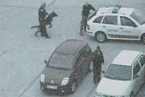 Strážníci zadržují muže, který se chtěl vloupat do auta.