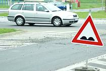 Značka upozorňující  na nerovnost vozovky varuje řidiče před propadlou silnicí před kruhovým objezdem.