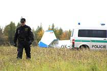 Policista hlídá okolí havarovaného stroje.