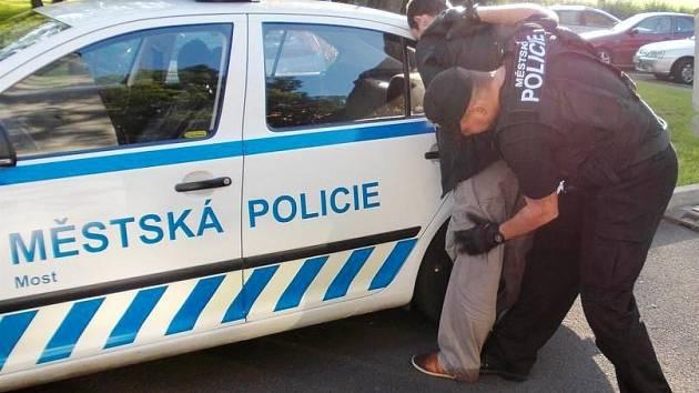 Mostecký strážník při zadržení pachatele.