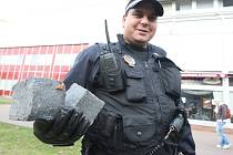 Litvínovský strážník s nalezenými dlažebními kostkami, které byly ukryté, pravděpodobně pro potřeby demonstrantů.