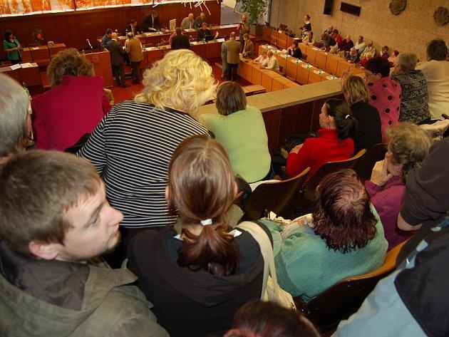 Jednání o prodeji bytů sledují desítky lidí z balkonu v zasedací síni.