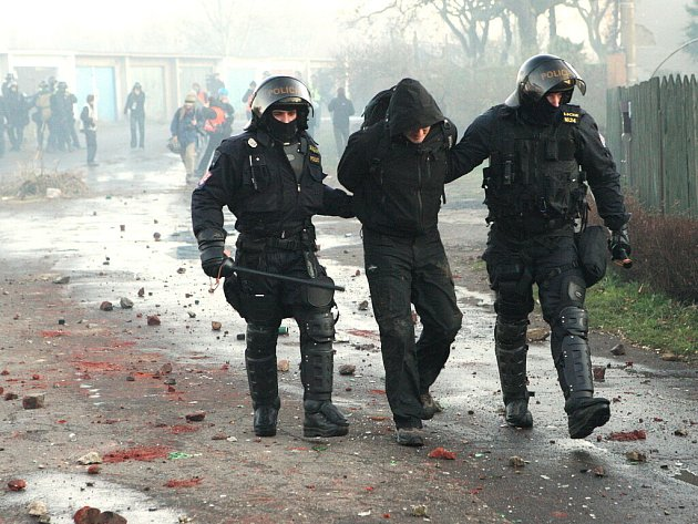 Policisté odvádějí jednoho z demonstrantů při listopadových nepokojích v Janově. Na zemi leží kusy cihel a kamení z rozebraných plotů při cestě.