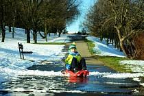 Osmiletý Martin bobuje na tajícím sněhu v parku pod nemocnicí.