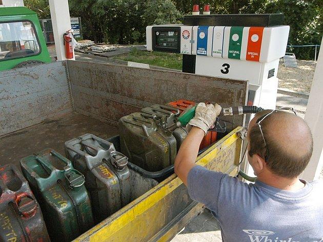 Muž tankuje u čerpací stanice do kanystrů.