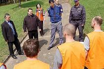 Primátor Mostu Vlastimil Vozka /druhý z leva/ děkuje věznům za pomoc při údržbě hřbitova. Vězně hlídá při práci dozorce.