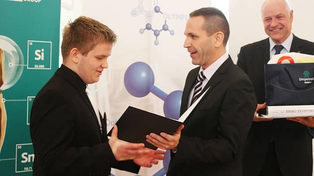 Předseda Ústřední komise chemické olympiády Petr Holzhauser předává ocenění vítězi kategorie A Richardu Veselému z Prahy.