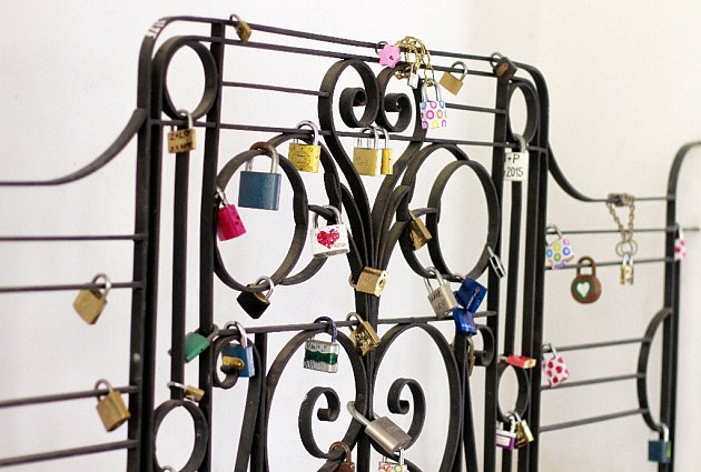 Na mříži vlitvínovském zámku visí přes 60různě barevných a ozdobených zámečků lásky.