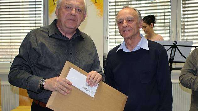 Vedoucí fotoklubu František Haase (vlevo) předává během slavnostního zahájení výstavy některé nevystavené fotografie Manfredu Hellmichovi. Ten patří ke skupině nadšenců, kteří se o kostel v Bedřichově Světci starali.