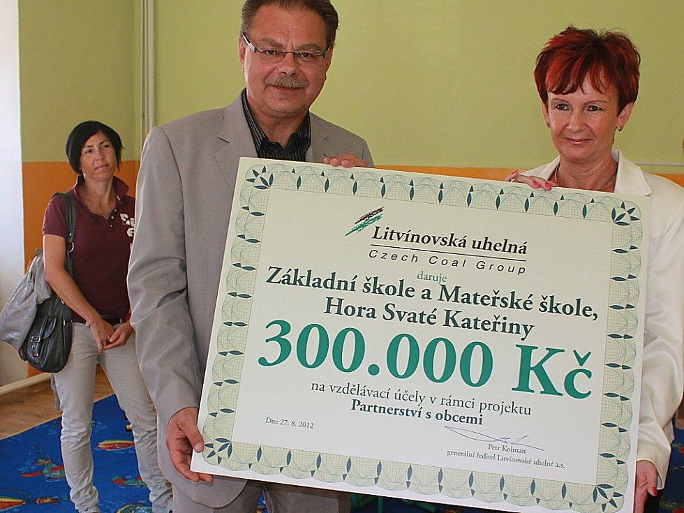 Generální ředitel Litvínovské uhelné Petr Kolman předává symbolický šek ředitelce školky Věře Sehnalové.