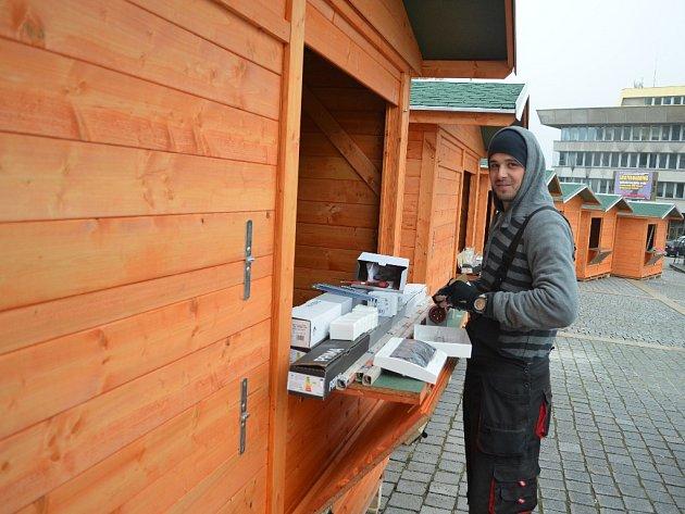 Roman Mrišo z firmy Elmosein.cz chystá s kolegy elektroinstalaci v nových stáncích na 1. náměstí v Mostě, kde rozsvěcením vánočního stromu začnou v neděli 27. listopadu Vánoční trhy.