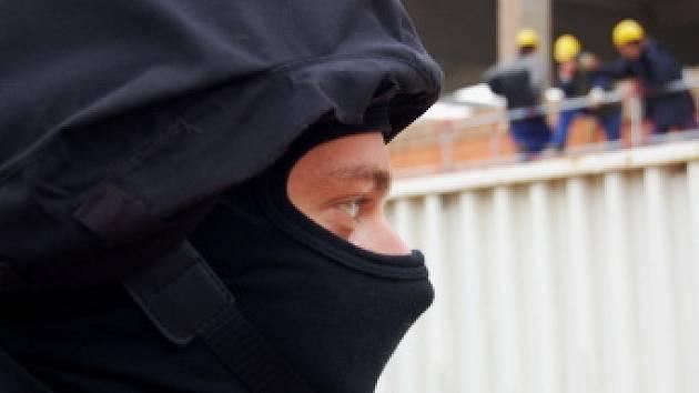"""Policista hlídá prostor před staveništěm, aby odtud neutíkali lidé, kteří pracují """"na černo"""""""