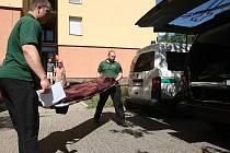 Pracovníci pohřební služby nakládají nosítka se zemřelou ženou.