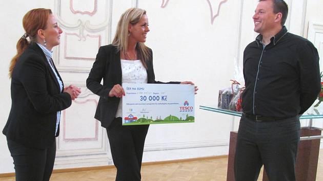 Karel Komárek převzal šek na třicet tisíc korun od šéfky litvínovského Tesca Pavly Kádnerové (uprostřed).              K předání došlo v  hlavním sále litvínovského zámku Valdštejnů. Byla u toho i starostka Litvínova Kamila Bláhová.