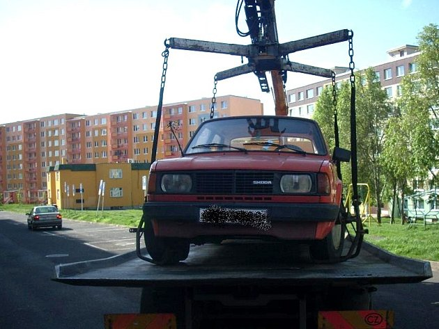 Odtahová služba nakládá automobil překážející čištění ulic na mosteckém sídlišti Výsluní.