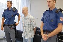 K soudu přivedla obžalovaného v poutech eskorta.