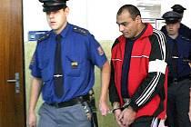 Věžeňská stráž přivádí do jednací saíně mosteckého soudu obžalovaného Miroslava Petera, který na Mostecku přepadl, znásilnil a ponižoval několik žen.