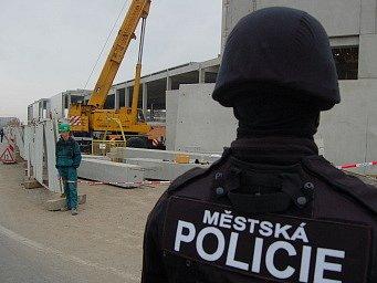 Strážník mostecké městské policie hlídá u brány na stavbu, aby někdo z nelegálně zaměstnaných neutekl.