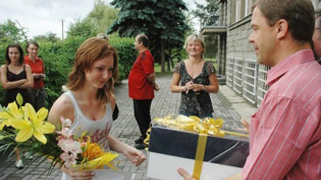 Anička Stellnerová přebírá od starosty dar a květinu.