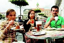 Rodina sedící na předzahrádce kavárny.