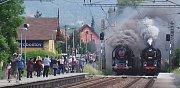 Souběžný průjezd dvou vlaků tažených parní lokomotivou zastávkou Proboštov.