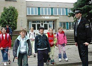 Před bílinskou školou hlídkuje strážník.