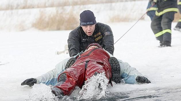 Mostečtí profesionální hasiči se státními policisty a mosteckými strážníky při včerejším nácviku záchrany tonoucího člověka na jezeře Matylda.
