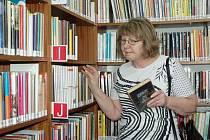 Olga Somolová vybírá knížky v Regionální knihovně Teplice.