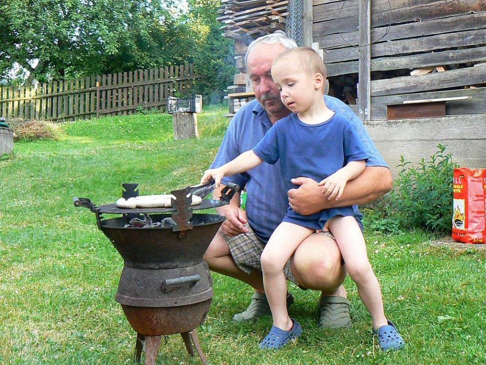 """Jan Kořínek - Jablonecko. S vnukem Matějem na chalupě na Sobotecku. """"Děda to fakt umí. Jednu bílou klobásku si dáváme jako zahřívací kolo a pak ještě masíčko. Osvědčila se nám krkovička marinovaná v koření a v medu alespoň dva dny."""""""