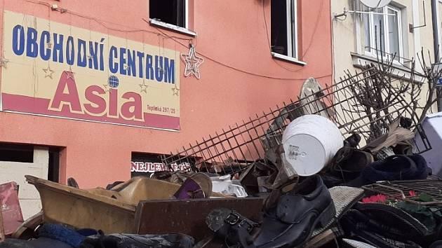 Lidé rozkrádají poničené zboží z vyhořelého obchodu v Duchcově