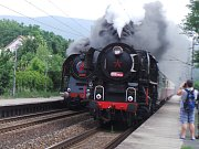 Souběžný průjezd dvou vlaků tažených parní lokomotivou zastávkou Proboštov