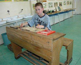 Žák v historické školní lavici.