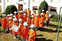 Přátelskou návštěvu z Nadace ČEZ přivítali děti i dospělí opravdu originálním způsobem. V oranžových tričkách a bílých přilbách zapůjčených z nedaleké Elektrárny Ledvice vytvořili veliké písmeno E.