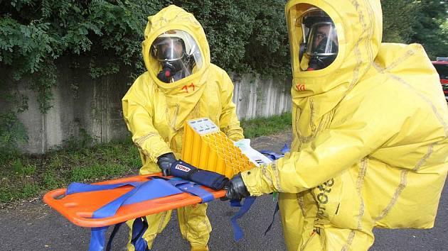Hasiči zasahují v protichemickém obleku u fiktivního úniku nebezpečné látky