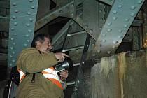 Jiří Pixa ze Správy mostů a tunelů Správy železniční a dopravní cesty Ústí nad Labem kontroluje rozsah poškození mostní konstrukce.