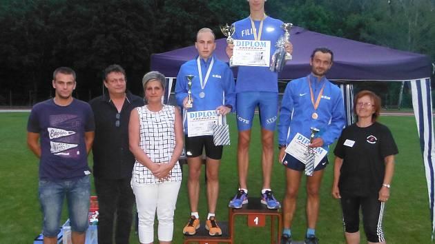 FILIP ŽIŽKA, nejrychlejší muž Podzimního běhu Bažantnicí s pohárem je na nejvyšším stupínku. Společně s ním pózují druhý Laštovka a třetí Krčmář. Vlevo rodina Šestáková, vpravo předsedkyně AK Duchcov Marie Polívková.