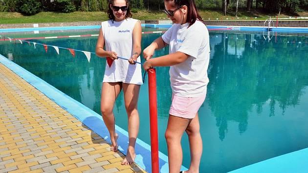 Plavčice Monika Novotná s Eliškou Vodraškovou upravují zábranu na koupališti v Duchcově