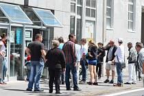 Skupina lidí čekajících na otevření magistrátu po polední pauze včera naproti Domu kultury v Teplicích.