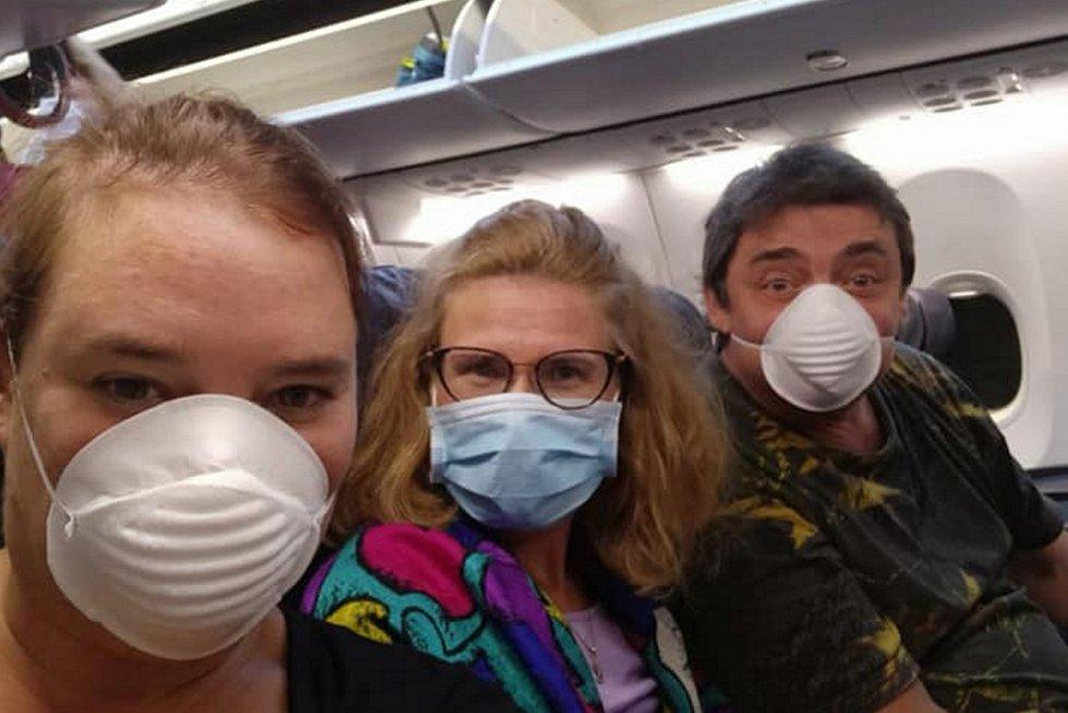 Zlata Biedermannová (uprostřed) v evakuačním letadle při návratu z Karibiku domů do Čech.