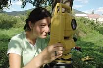 Studentka geodézie zaměřuje pavilonek v zahradě oseckého kláštera.