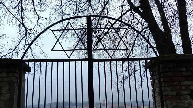 Pohled ze židovského hřbitova skrz hlavní, pro vstup nepoužívanou bránu na Poběžovice.