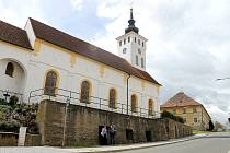 Kostel svatého Jiřího v Koutě na Šumavě stojí na pivovarských sklepech. U vchodu do podzemních chodeb stojí Anna Váchalová a starosta obce Bohuš Havlovic.