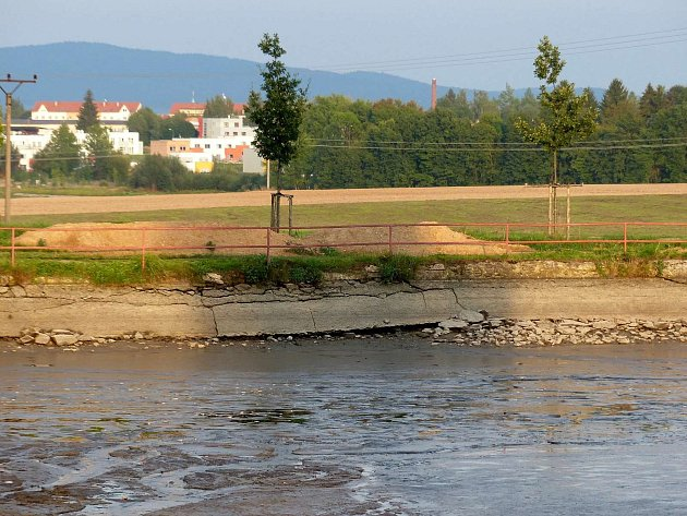 Petrovický rybník čeká na opravu. Zbavený vody nabízí zejména pohled na popraskanou a drolící se hráz.