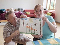 Manželé Šleglovi ukazují obrázek, který jim namalovala a darovala malá holčička