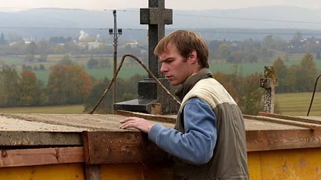 KONTROLA PROVEDENÝCH PRACÍ. Odřich Kovařík ml. kontroluje opravenou, dosud ´zašalovanou´ část klenečské hřbitovní zdi.
