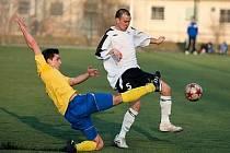 Benešovský Marek Večera (ve žlutém) odehrává míč před hornoměcholupským Jaroslavem Procházkou.