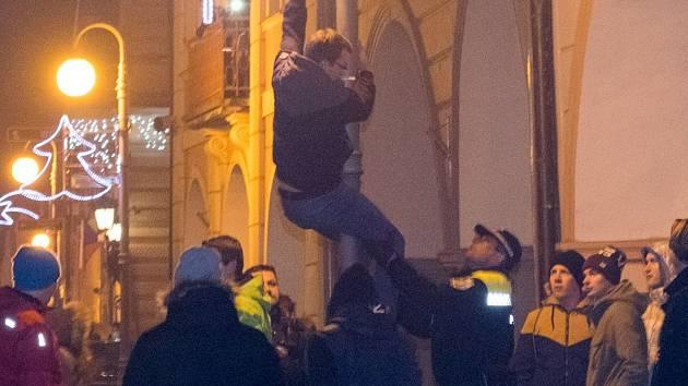 Slezte z té lampy! Mladý muž se snažil vyšplhat na veřejné osvětlení.