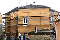 BUDOVA BÝVALÉ DRAŽENOVSKÉ ŠKOLY, kde dnes sídlí obecní úřad, pošta a mateřská škola Benjamínek, je obehnaná lešením. Už jsou vidět první opravená místa fasády.