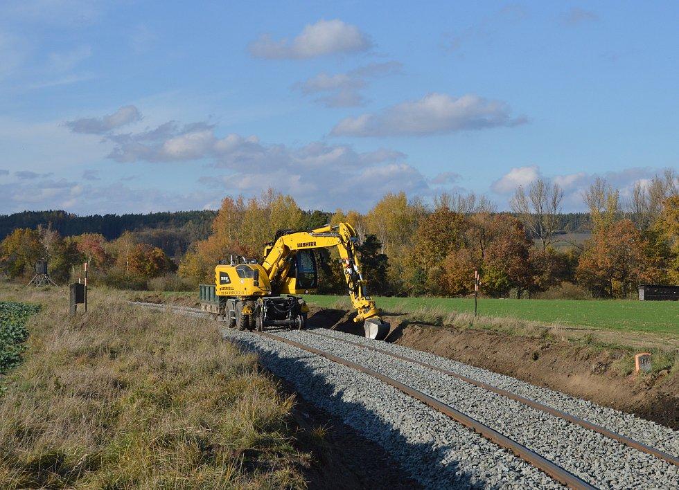 Další bagr provádí stavební práce na odvodňovacím příkopu.