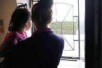 Napadená žena s tříletou dcerkou  stojí u okna, kde k útoku slzným plynem došlo.